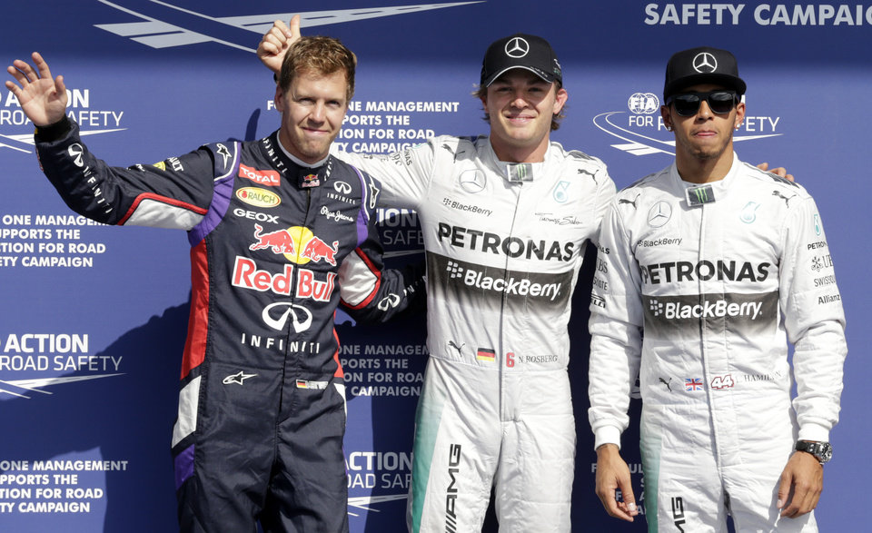 Photo - Mercedes driver Nico Rosberg of Germany, center, shows thumb up after he qualified for pole position, ahead of Sunday's Belgian Formula One Grand Prix in Spa-Francorchamps, Belgium, Saturday, Aug. 23, 2014. Mercedes driver Lewis Hamilton of Britain, right, placed second, Red Bull driver Sebastian Vettel of Germany, left, will leave from third place. (AP Photo/Yves Logghe)