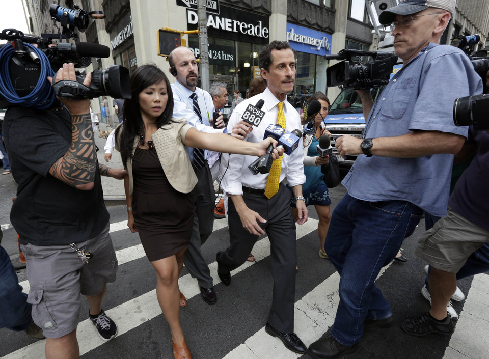 Photo - New York City mayoral candidate Anthony Weiner is pursued by reporters in New York on Wednesday, July 24, 2013. The former congressman acknowledged sending explicit text messages to a woman as recently as last summer, more than a year after sexting revelations destroyed his congressional career. (AP Photo/Richard Drew)