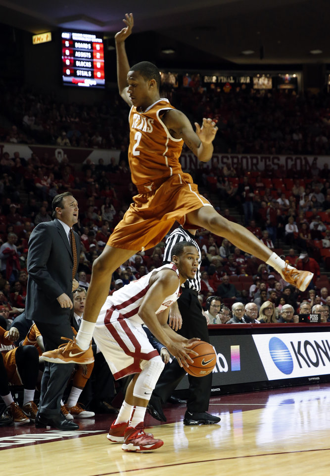 Photo - Texas Demarcus Holland leaps on a pump fake by Oklahoma Sooner Jordan Woodard (10) as the University of Oklahoma Sooners (OU) men play the Texas Longhorns (TU) in NCAA, college basketball at The Lloyd Noble Center on Saturday, March 1, 2014  in Norman, Okla. Photo by Steve Sisney, The Oklahoman
