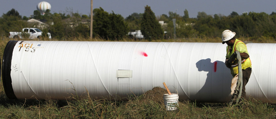 Workers install a pipeline on the east side of Will Rogers World Airport, readying the area for development. Photos by Steve Gooch, The Oklahoman
