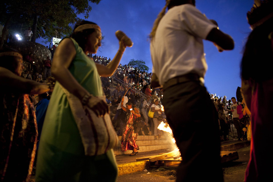 Indigenous supporters of Venezuela's President Hugo Chavez dance around a bonfire during a vigil to pray for Chavez as he remains in a hospital undergoing cancer treatment in Caracas, Venezuela, Friday, Feb. 22, 2013. Chavez hasn't been seen since he returned to Venezuela on Monday from Cuba, where for 10 weeks he was recovering and fighting complications following his latest cancer surgery Dec. 11. (AP Photo/Ariana Cubillos)