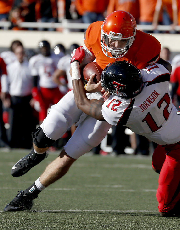 Photo - Oklahoma State's J.W. Walsh (4) is tackled by Texas Tech's D.J. Johnson (12) during a college football game between Oklahoma State University and the Texas Tech University (TTU) at Boone Pickens Stadium in Stillwater, Okla., Saturday, Nov. 17, 2012. Photo by Sarah Phipps, The Oklahoman