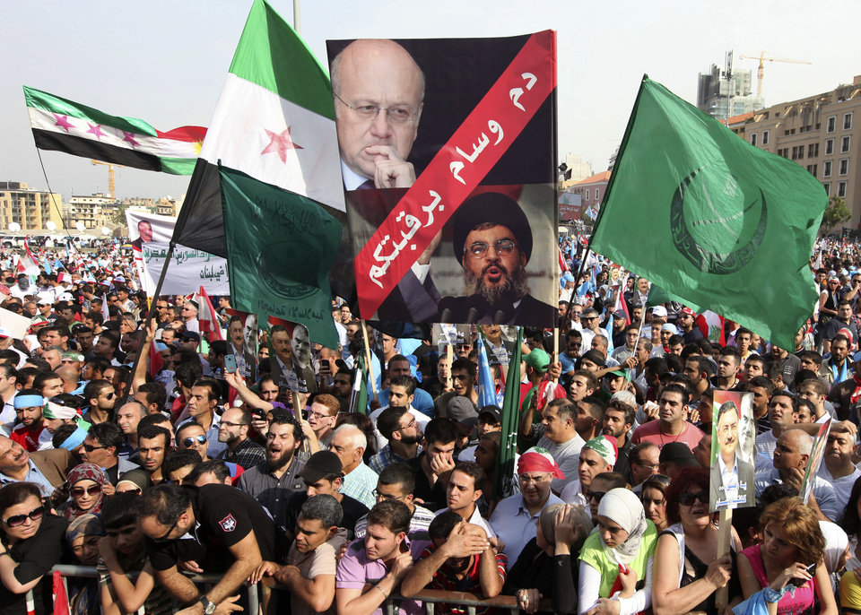 Photo -   In this picture taken on Sunday October 21, 2012, anti-Lebanese government protesters, wave the Syrian revolutionary flags and hold portraits of Lebanese Prime Minister Najib Mikati, up, and for Hezbollah's leader Sheik Hassan Nasrallah, down, with Arabic words read: