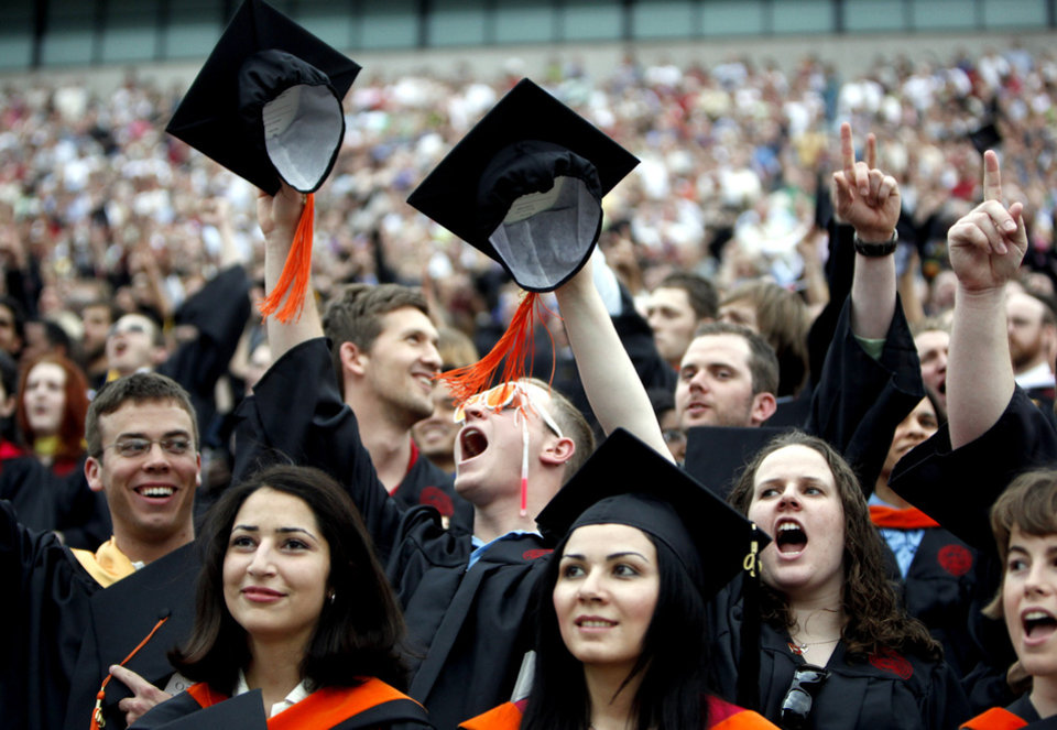 Photo - Robert Hudkins of Broken Arrow, Okla.,  center, cheers during the 2009 University of Oklahoma Spring Commencement at The Gaylord Family Oklahoma - Memorial Stadium, Friday, May 15, 2009, in Norman, Okla. Photo by Sarah Phipps, The Oklahoman