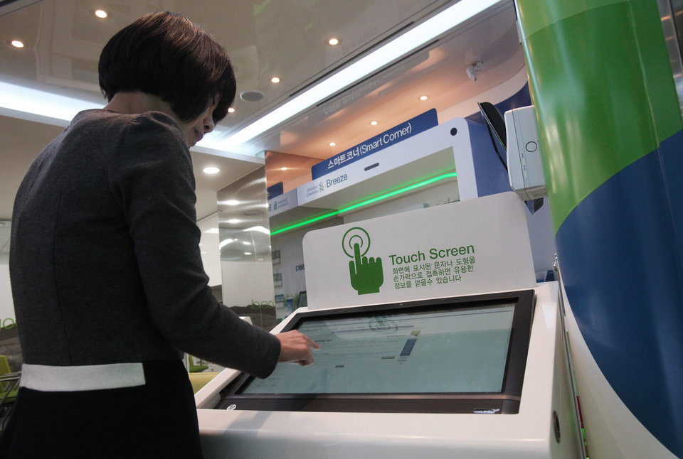 In this Friday, Jan. 11, 2013 photo, customer Eun-young does banking through a computer monitor at a Smart Banking Center of Standard Chartered Bank in Seoul, South Korea. In an age when checks can be deposited by smartphone and almost everyone retrieves cash from ATMs, the corner bank can seem a relic, with its paper deposit slips (AP Photo/Ahn Young-joon)
