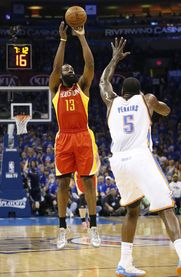 Photo - Houston Rockets guard James Harden (13) shoots over Oklahoma City Thunder center Kendrick Perkins (5) in the first quarter of Game 5 of a first-round NBA basketball playoff series in Oklahoma City, Wednesday, May 1, 2013. (AP Photo/Sue Ogrocki)