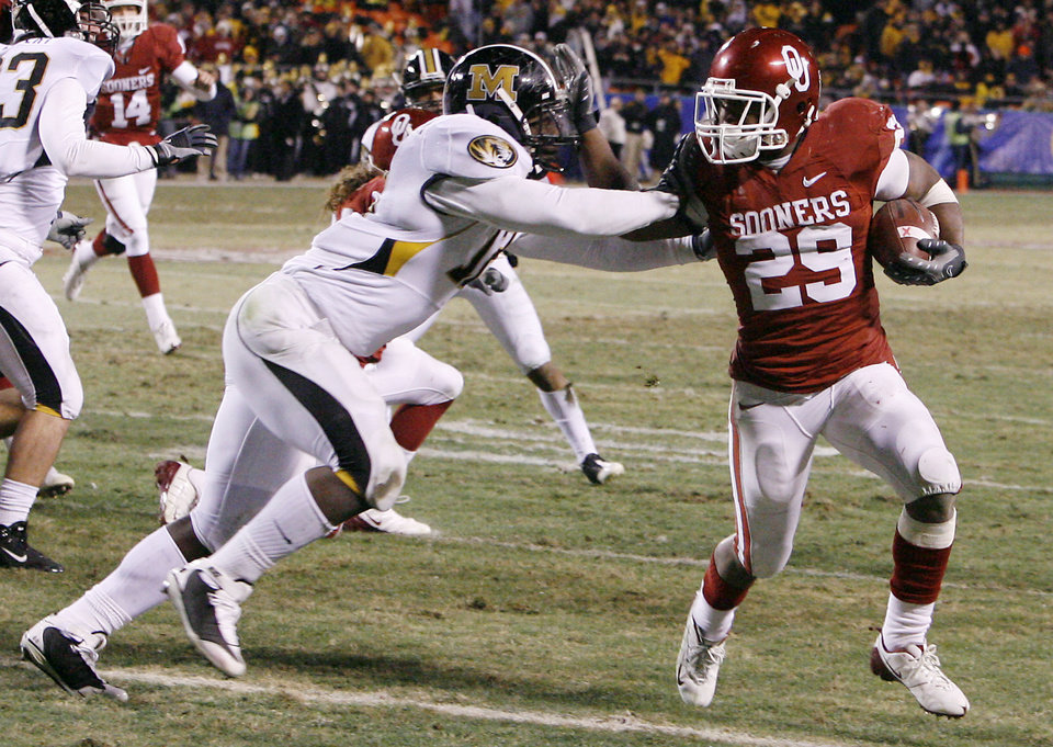 Photo - Oklahoma's Chris Brown (29) stiff arms Missouri's Sean Weatherspoon (12) for more yardage during the first half of the Big 12 Championship college football game between the University of Oklahoma Sooners (OU) and the University of Missouri Tigers (MU) on Saturday, Dec. 6, 2008, at Arrowhead Stadium in Kansas City, Mo.   PHOTO BY NATE BILLINGS, THE OKLAHOMAN  ORG XMIT: KOD