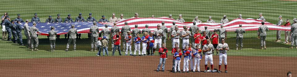 A huge American Flag is unfurled by military personnell on Armed Forces Awareness Day as the University of Oklahoma (OU) Sooners play New Orleans in NCAA college baseball at L. Dale Mitchell Field on Saturday, April 20, 2013 in Norman, Okla.  Photo by Steve Sisney, The Oklahoman