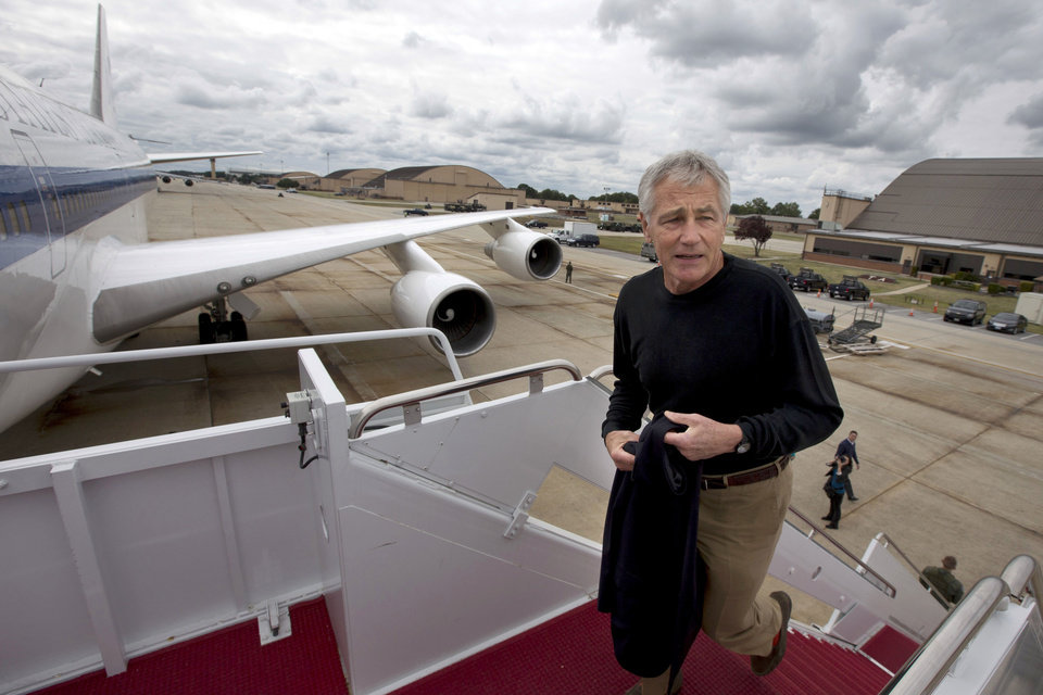 Photo - FILE - In this Sept. 28, 2013, file photo U.S. Secretary of Defense Chuck Hagel boards his plane at Andrews Air Force Base, Md., en route to South Korea. Saturday, Oct. 5, 2013, the Pentagon ordered most of its approximately 400,000 furloughed civilian employees back to work. The decision by Hagel is based on a Pentagon legal interpretation of a law called the Pay Our Military Act. That measure was passed by Congress and signed by President Barack Obama shortly before the partial government shutdown began Tuesday, Oct. 1. The Pentagon did not immediately say on Saturday exactly how many workers will return to work, but use the term