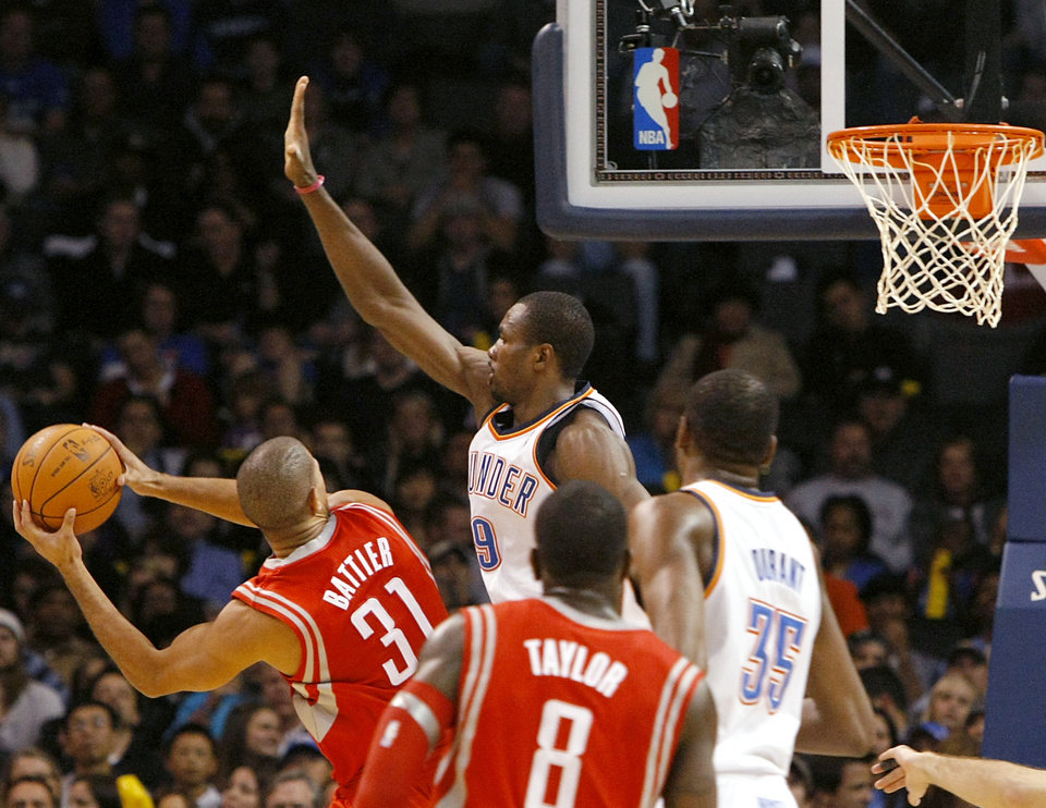 Photo - Oklahoma City's Serge Ibaka pressures a shot by Houston's Shane Battier during their NBA basketball game at the OKC Arena in downtown Oklahoma City on Wednesday, Nov. 17, 2010. Photo by John Clanton, The Oklahoman