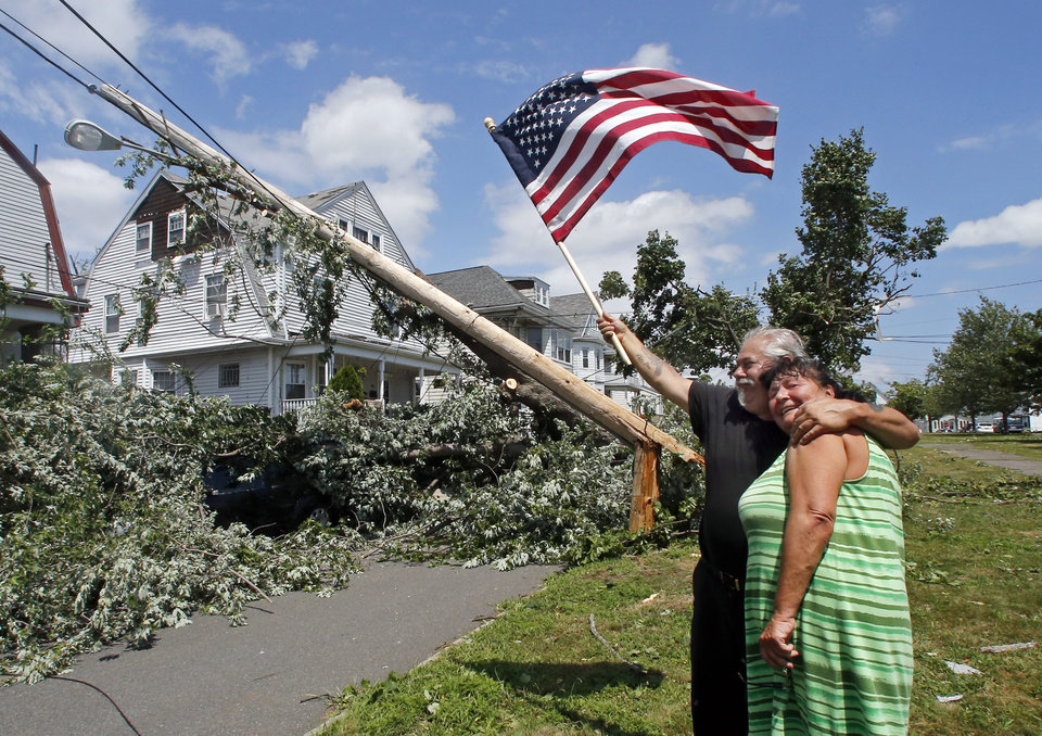 Photo - Homeowner Lenny DiBartolomeo hugs his neighbor Jeanie Stornaiuolo while waving a flag in Revere, Mass., Monday, July 28, 2014 after a tornado touched down. Both said they were grateful that they knew of no injuries despite the damage to their homes. (AP Photo/Elise Amendola)