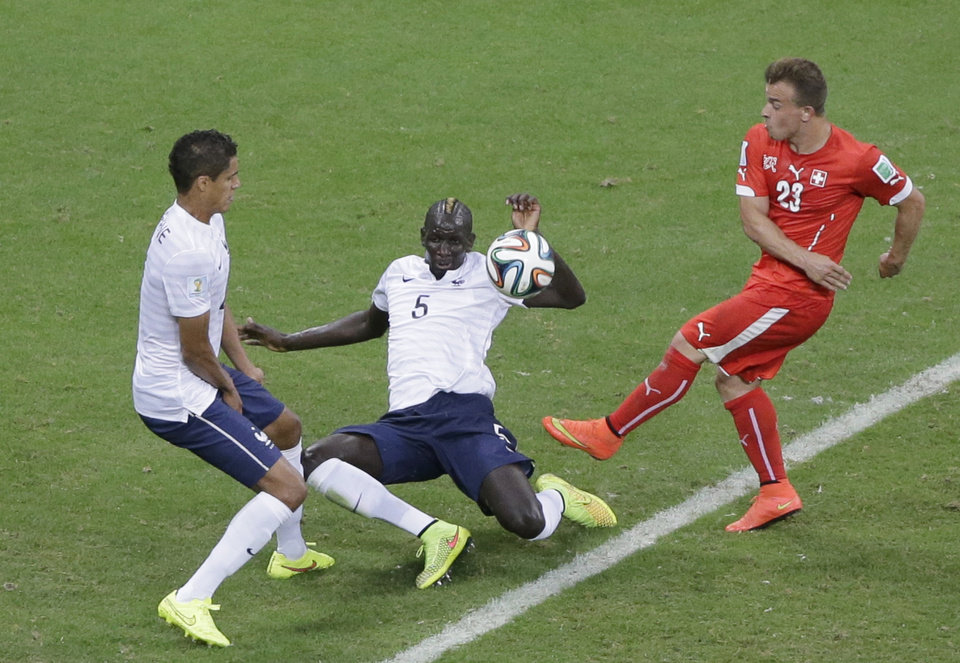 Photo - France's Mamadou Sakho, center, blocks a shot by Switzerland's Xherdan Shaqiri during the group E World Cup soccer match between Switzerland and France at the Arena Fonte Nova in Salvador, Brazil, Friday, June 20, 2014. (AP Photo/Sergei Grits)