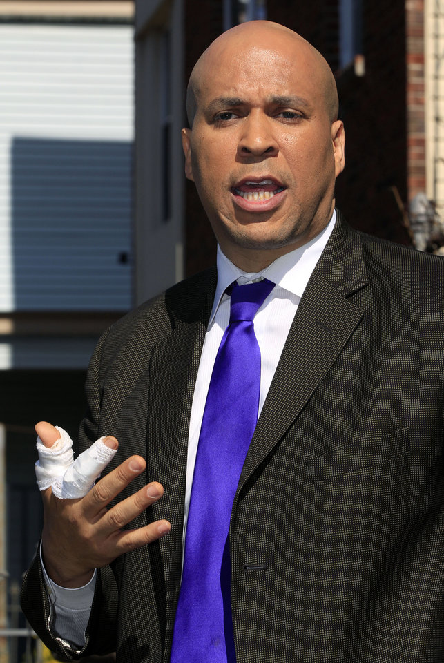 Photo -   Newark Mayor Cory Booker stands in front of a boarded-up 433 Hawthorne Avenue in Newark, N.J., Friday, April 13, 2012 as he talks about rescuing a neighbor Thursday from a fire at the home. Boooker said Friday he feared for his life as he helped rescue a neighbor from a fire before firefighters arrived. He described how he returned home Thursday night and saw his neighbor's home engulfed in flames. The woman Booker helped save is in stable condition. (AP Photo/Mel Evans)