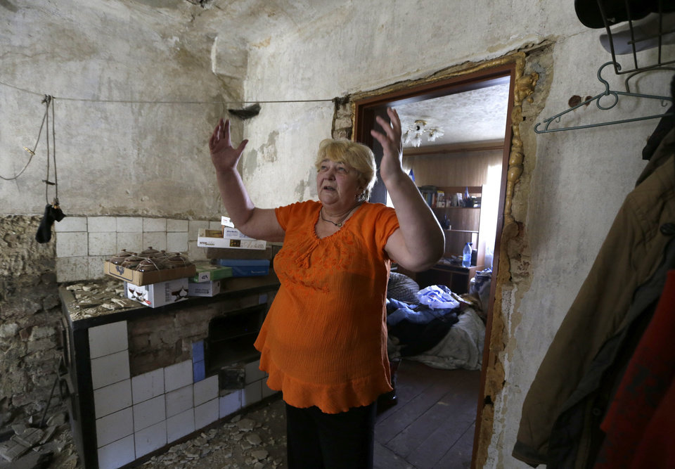 Photo - Local resident Valentina Smirnova reacts as she stands in her destroyed house after shelling in Donetsk, eastern Ukraine, Thursday, Aug. 14, 2014. A rebel-held city in eastern Ukraine came under intensified shelling Wednesday as the U.N. revealed that the death toll from the fighting between government troops and separatists has nearly doubled in the last two weeks. (AP Photo/Sergei Grits)
