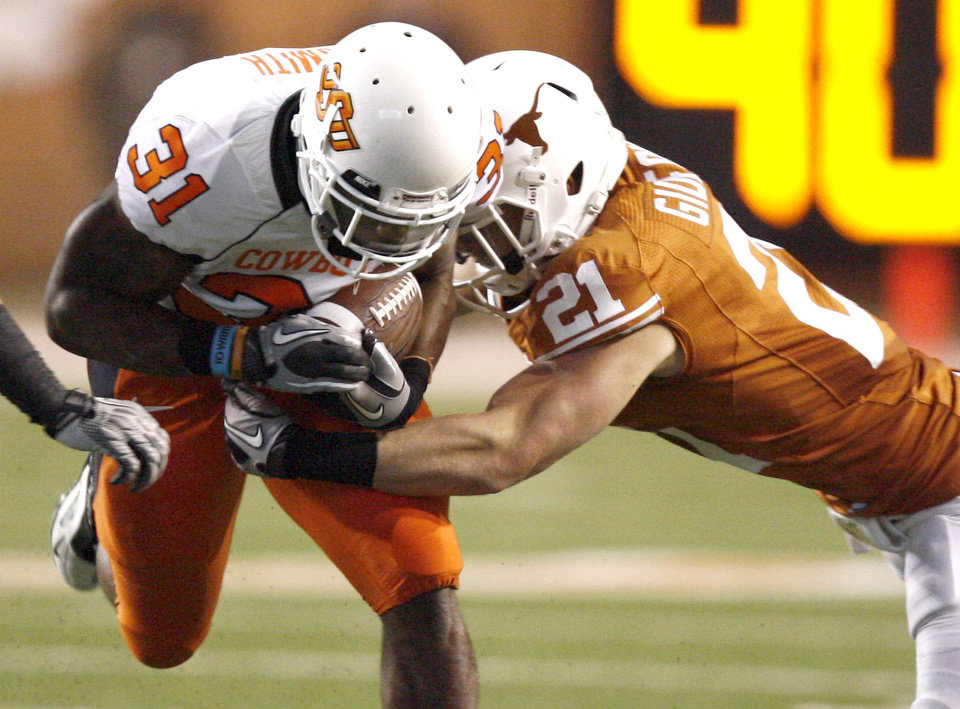 Photo - Oklahoma State's Jeremy Smith (31) is tackled by Texas' Blake Gideon (21) during the college football game between the Oklahoma State University Cowboys (OSU) and the University of Texas Longhorns (UT) at Darrell K Royal-Texas Memorial Stadium in Austin, Texas, Saturday, November 13, 2010. Photo by Sarah Phipps, The Oklahoman