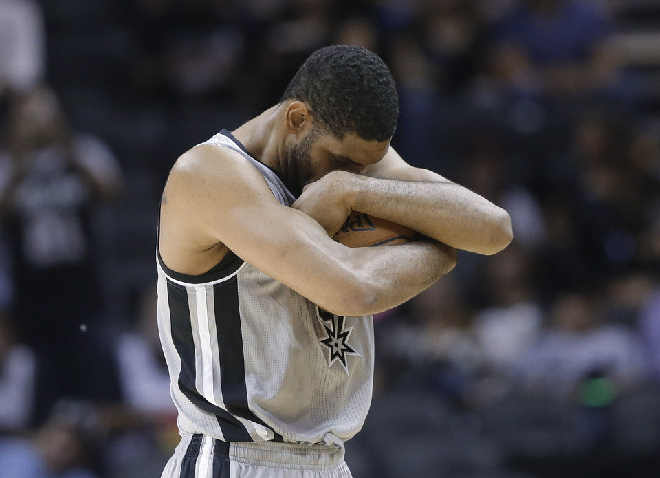 Photo - San Antonio Spurs' Tim Duncan clutches the ball prior to the tip-off of the team's NBA basketball game against the Memphis Grizzlies, Wednesday, Oct. 30, 2013, in San Antonio. Duncan left the game in the second half with a chest injury. (AP Photo/Eric Gay)