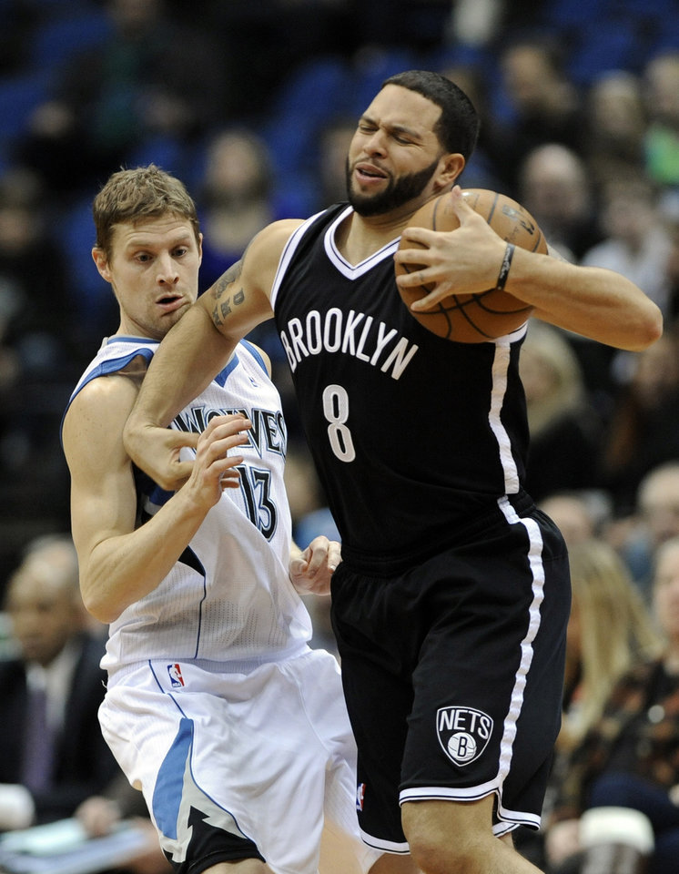 Photo - Minnesota Timberwolves' Luke Ridnour, left, gets an elbow to the chin as he defends against Brooklyn Nets' Deron Williams in the first half of an NBA basketball game on Wednesday, Jan. 23, 2013, in Minneapolis. (AP Photo/Jim Mone)