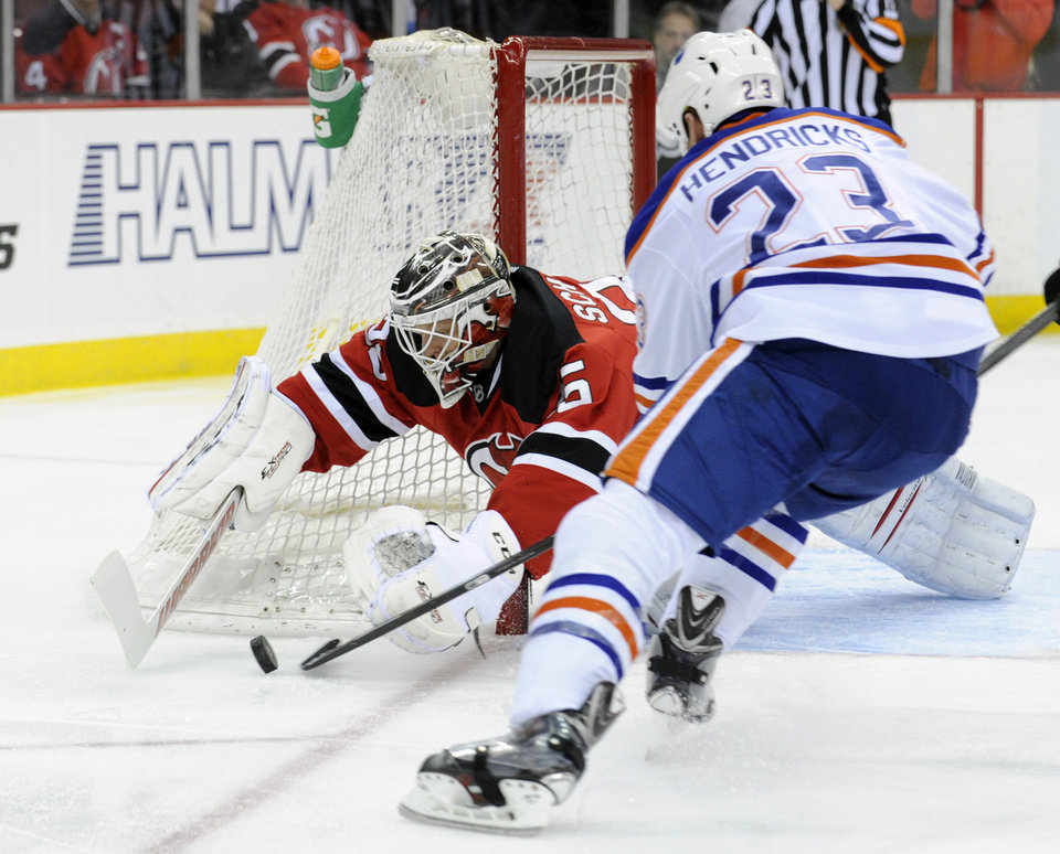 Photo - New Jersey Devils goaltender Cory Schneider, left, dives to cover the puck as Edmonton Oilers' Matt Hendricks (23) attempts to get a stick on it during the first period of an NHL hockey game on Friday, Feb. 7, 2014, in Newark, N.J. (AP Photo/Bill Kostroun)