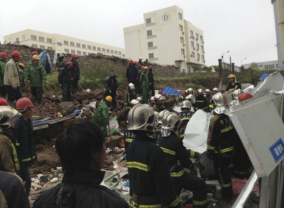 Photo - In this photo taken by mobile phone, rescuers and workers conduct a search operation following a wall collapse in Qingdao in east China's Shandong province Sunday, May 11, 2014. The wall collapse triggered by heavy rains at a recycling plant killed 18 people and injured three others early Sunday in the eastern city of Qingdao, state media reported. (AP Photo) CHINA OUT