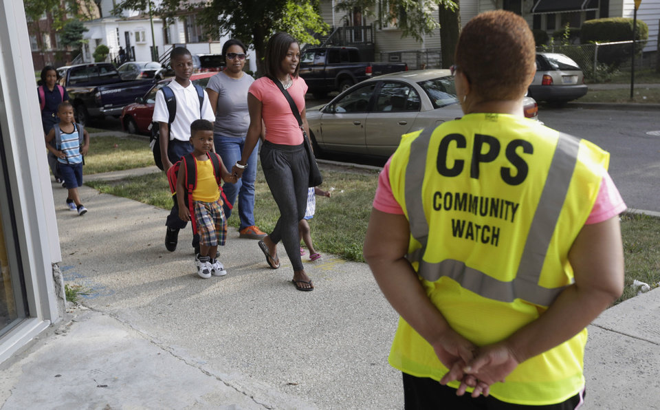 Photo - ADVANCE FOR USE SUNDAY, DEC. 22 AND THEREAFTER - FILE - In this Aug. 26, 2013 file photo, safety guard Renee Green watches as parents walk with their children on the first day of school in Chicago. The Chicago Public Schools announced in May it would close about 50 schools and programs to deal with a budget deficit and lower attendance numbers, The closures forced many children to walk designated
