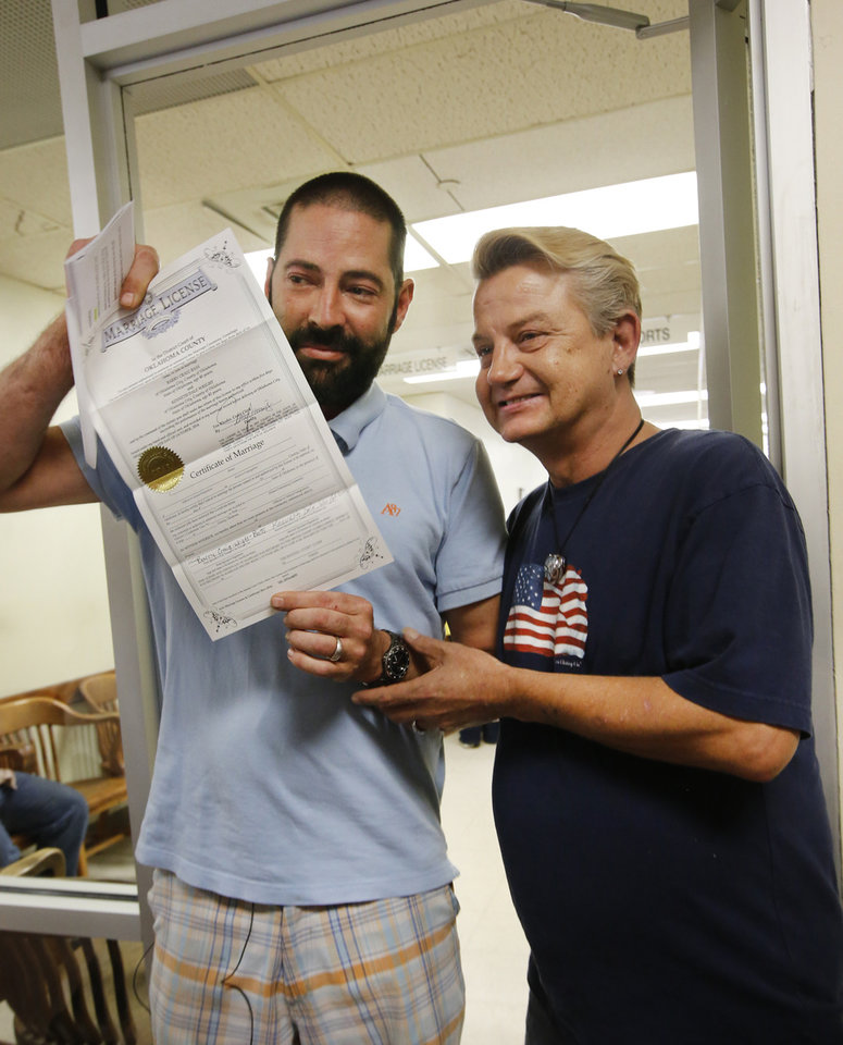 Photo - Kenny Wright, left, and Bo Bass show their marriage license to members of the media at the Oklahoma County Courthouse in Oklahoma City, Monday October, 6 2014.They were the 3rd same sex couple to receive a marriage license in Oklahoma County. Photo By Steve Gooch, The Oklahoman