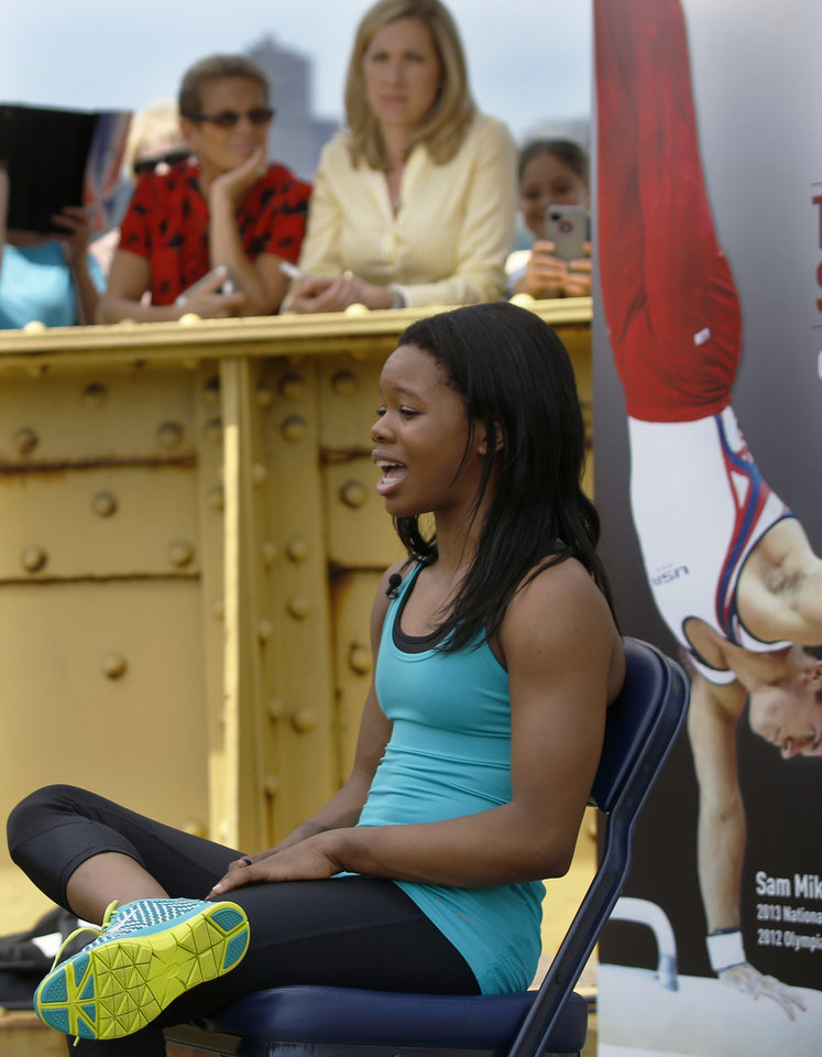 Photo - Olympic women's gymnastics champion Gabrielle Douglas is interviewed Monday, June 23, 2014, in Pittsburgh. Douglas is hoping to return to competition at USA Gymnastics national championships in Pittsburgh in August. In the background are people who were had gathered to watch an attempt nearby to set a record for most simultaneous cartwheels. (AP Photo/Keith Srakocic)