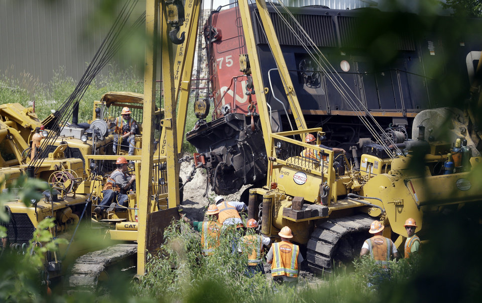 Photo - Workers clean up a train derailment Monday, July 21, 2014, in Slinger, Wis. A southbound Canadian National train struck several Wisconsin & Southern Railroad cars around 8:30 p.m. Sunday at a rail crossing in Slinger, Wic.,according to Patrick Waldron, a Canadian National spokesman. The derailment injured at least two people and spilled thousands of gallons of fuel that prompted the evacuation of dozens of homes, but evacuees were allowed to return around 1:30 a.m. Monday, Slinger Fire Chief Rick Hanke said. (AP Photo/Morry Gash)