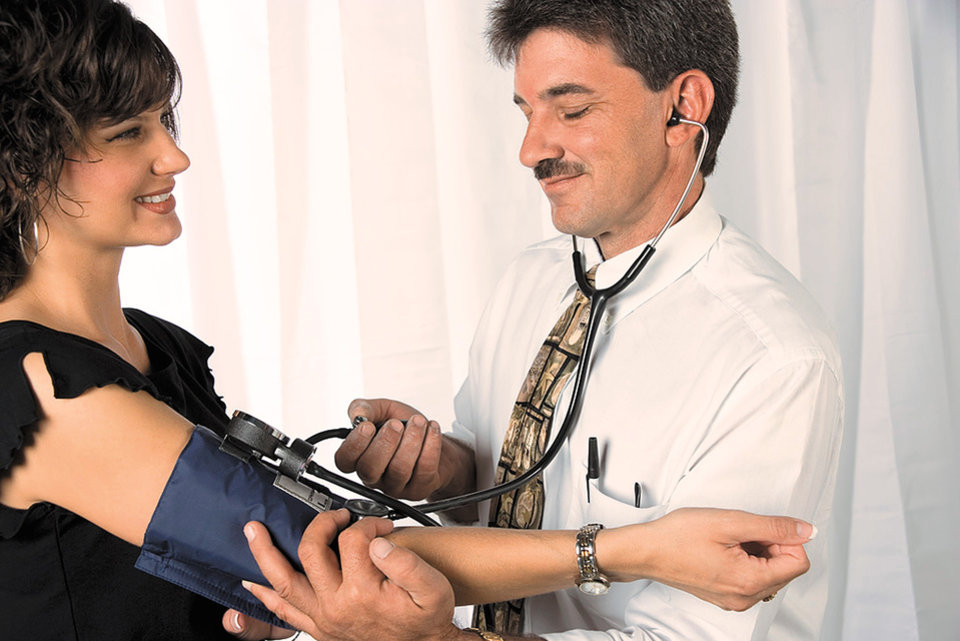 Photo - Woman getting blood pressure taken by doctor