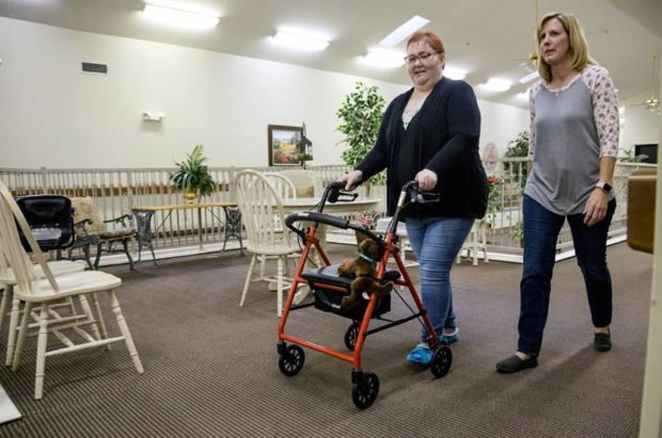 Photo -  Dana Dixon, left, talks with Becky Wilkinson as they walk through the hallway at Heritage Assisted Living Center in Yukon. [Photo by Chris Landsberger, The Oklahoman]