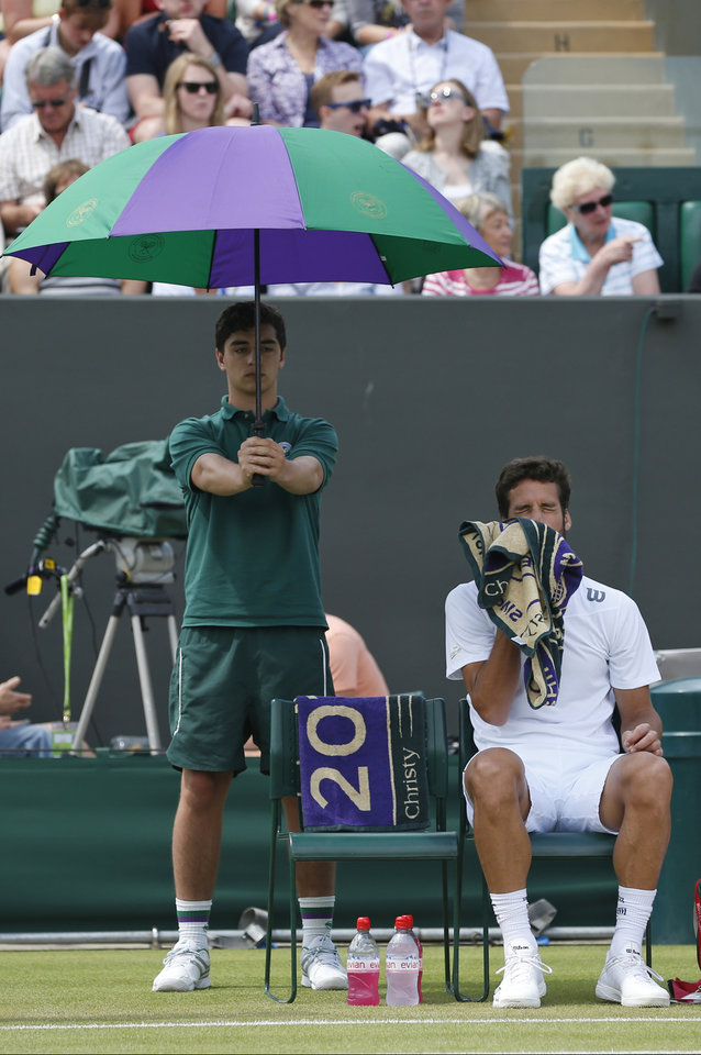 Photo - Feliciano Lopez of Spain wipes his face with a towel during a game break as he plays John Isner of the U.S. during their men's singles match at the All England Lawn Tennis Championships in Wimbledon, London, Monday, June 30, 2014. (AP Photo/Pavel Golovkin)