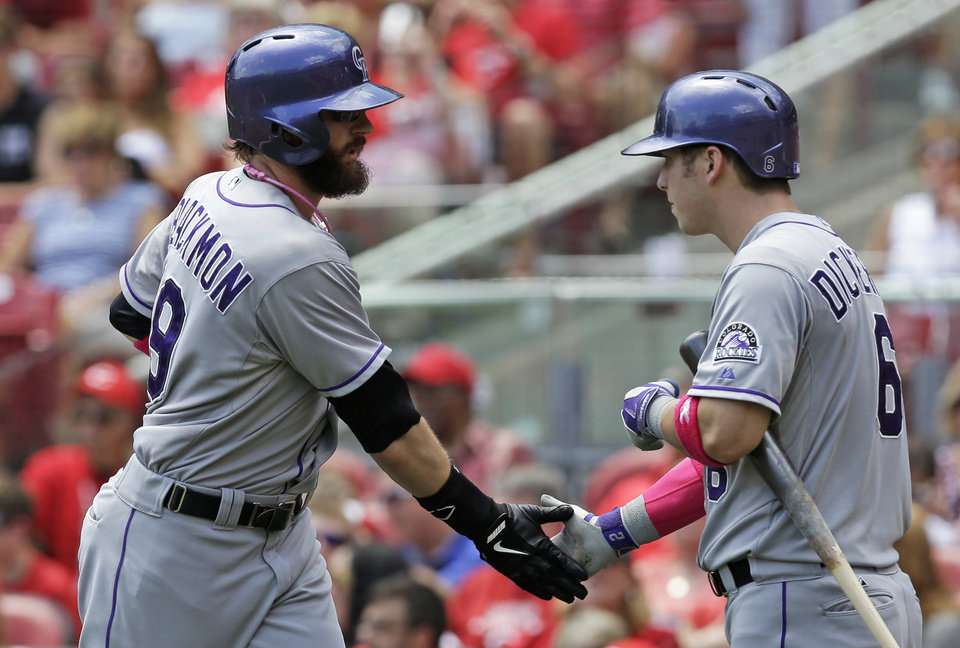 Photo - Colorado Rockies' Corey Dickerson, right, congratulates Charlie Blackmon, left,  after Blackmon hit a solo home run off Cincinnati Reds starting pitcher Homer Bailey in the fourth inning of a baseball game, Sunday, May 11, 2014, in Cincinnati. (AP Photo/Al Behrman)