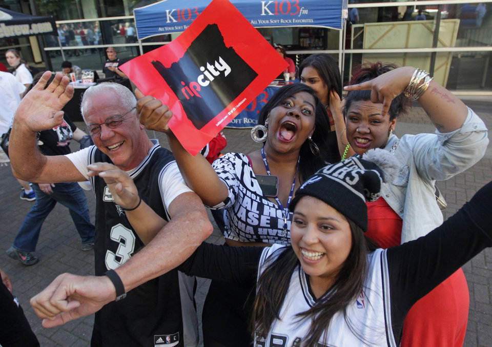 Photo - San Antonio Spurs fans James Lull, left, Dulce Barraza, right, pose for a photo with Portland Trail Blazers fans Mae Mae Gipson, cq, center, Olyvia Batson, right rear, before Game 4 of a Western Conference semifinal NBA basketball playoff series Monday, May 12, 2014, in Portland, Ore. (AP Photo/Rick Bowmer)