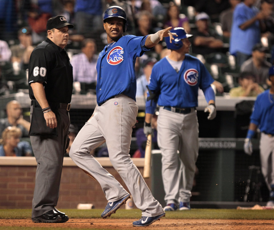 Photo - Chicago Cubs' Starlin Castro (13) points to first base after Castro scored on a single by Ryan Sweeney in the 11th inning of a baseball game against the Colorado Rockies in Denver on Tuesday, Aug. 5, 2014. (AP Photo/Joe Mahoney)