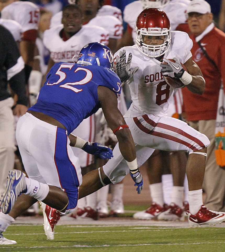 Photo - Oklahoma's Dominique Whaley (8) runs past Kansas' Steven Johnson (52) during the college football game between the University of Oklahoma Sooners (OU) and the University of Kansas Jayhawks (KU) on Saturday, Oct. 15, 2011. in Lawrence, Kan. Photo by Chris Landsberger, The Oklahoman