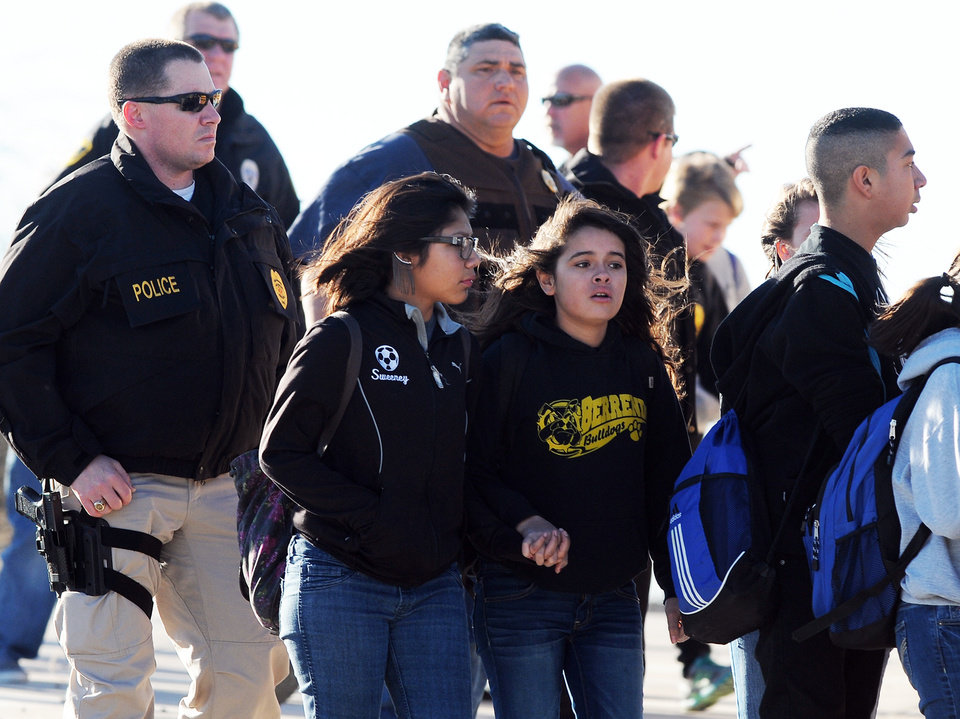 Photo - Students surrounded by officials are escorted from Berrendo Middle School after a shooting, Tuesday, Jan. 14, 2014, in Roswell, N.M. Roswell police said the suspected shooter was arrested at the school, but authorities have not said if there were any injuries. The school has been placed on lockdown. No other details are yet available. (AP Photo/Roswell Daily Record, Mark Wilson)