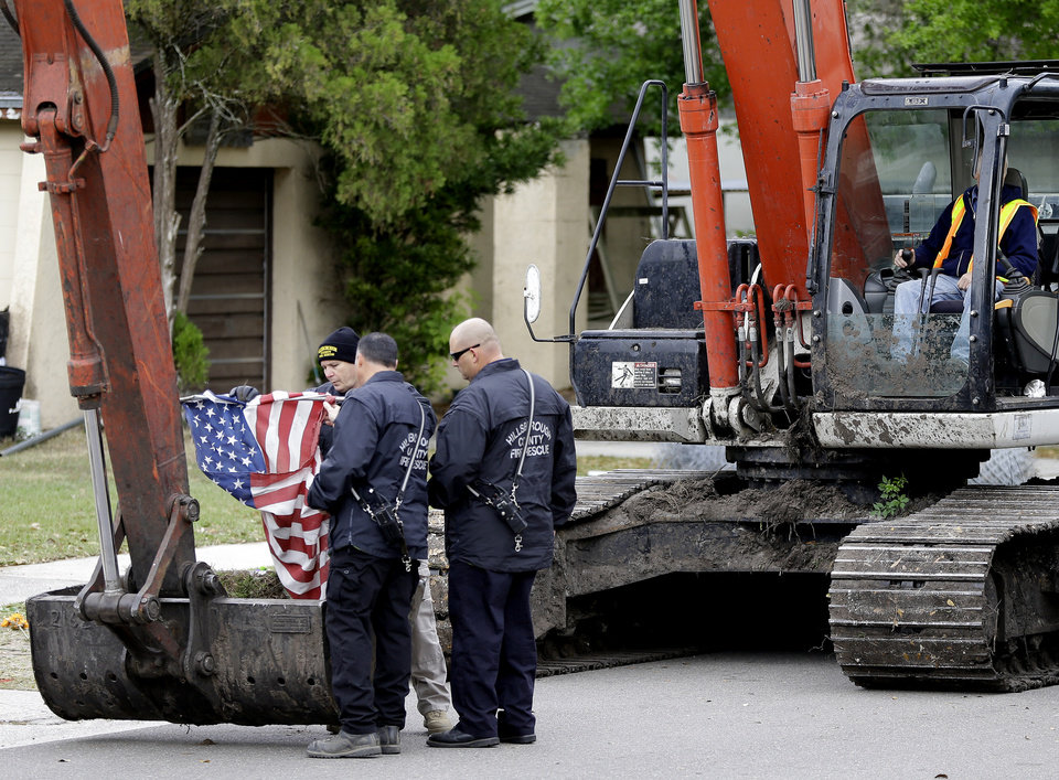 Photo - Hillsborough County, Fla., firefighters fold an American flag after removing it from a home is being destroyed Sunday, March 3, 2013, after a sinkhole opened up underneath a bedroom late Thursday evening and swallowed a man in Seffner, Fla. (AP Photo/Chris O'Meara)