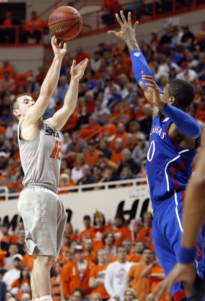 Photo - OSU's Keiton Page (12) shoots a 3-point shot over KU's Thomas Robinson (0) in the second half during a men's college basketball game between the Oklahoma State University Cowboys and the University of Kansas Jayhawks at Gallagher-Iba Arena in Stillwater, Okla., Monday, Feb. 27, 2012. KU won, 70-58. Photo by Nate Billings, The Oklahoman