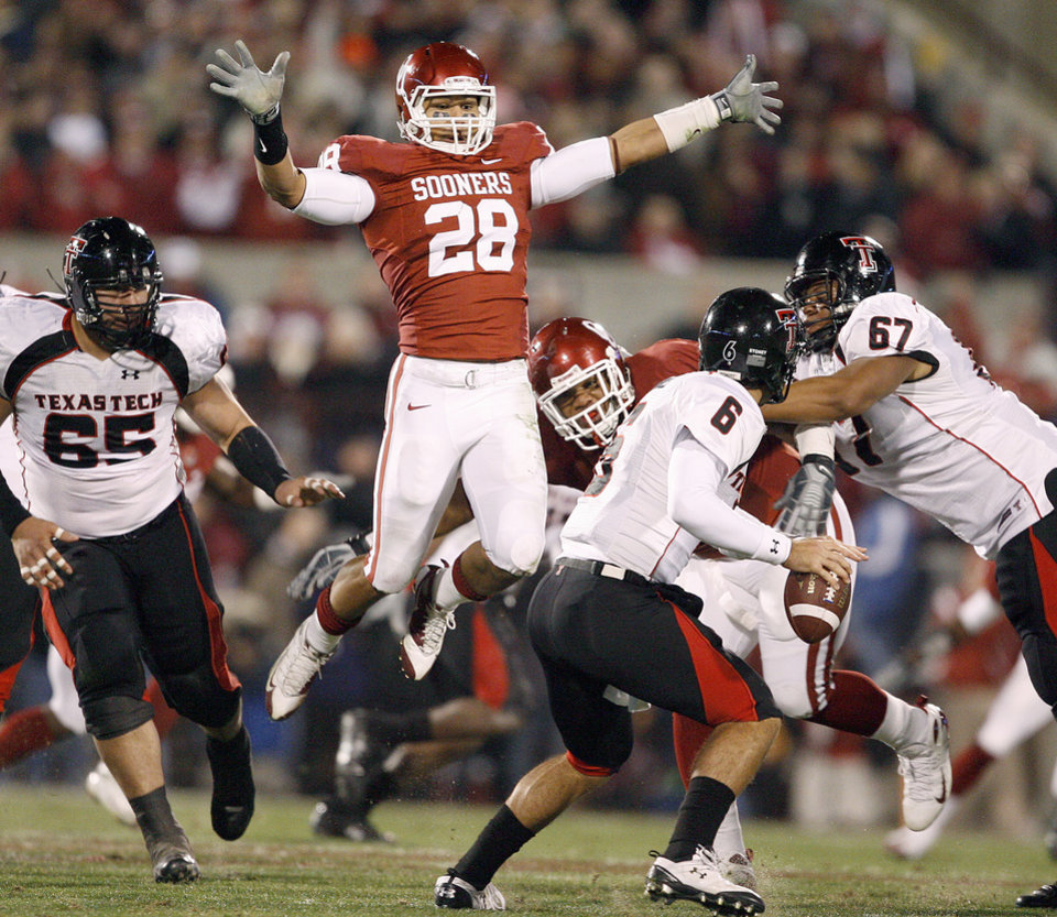 OU\'s Travis Lewis leaps at Graham Harrell of Texas Tech during the college football game between the University of Oklahoma Sooners and Texas Tech University at Gaylord Family -- Oklahoma Memorial Stadium in Norman, Okla., Saturday, Nov. 22, 2008. BY BRYAN TERRY, THE OKLAHOMAN