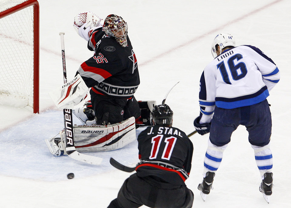 Photo - Carolina Hurricanes' Justin Peters (35) deflects the shot of Winnipeg Jets' Andrew Ladd (16) wide of the net with Hurricanes Jordan Staal (11) nearby during the second period of an NHL hockey game, Tuesday, March 26, 2013, in Raleigh, N.C. (AP Photo/Karl B DeBlaker)