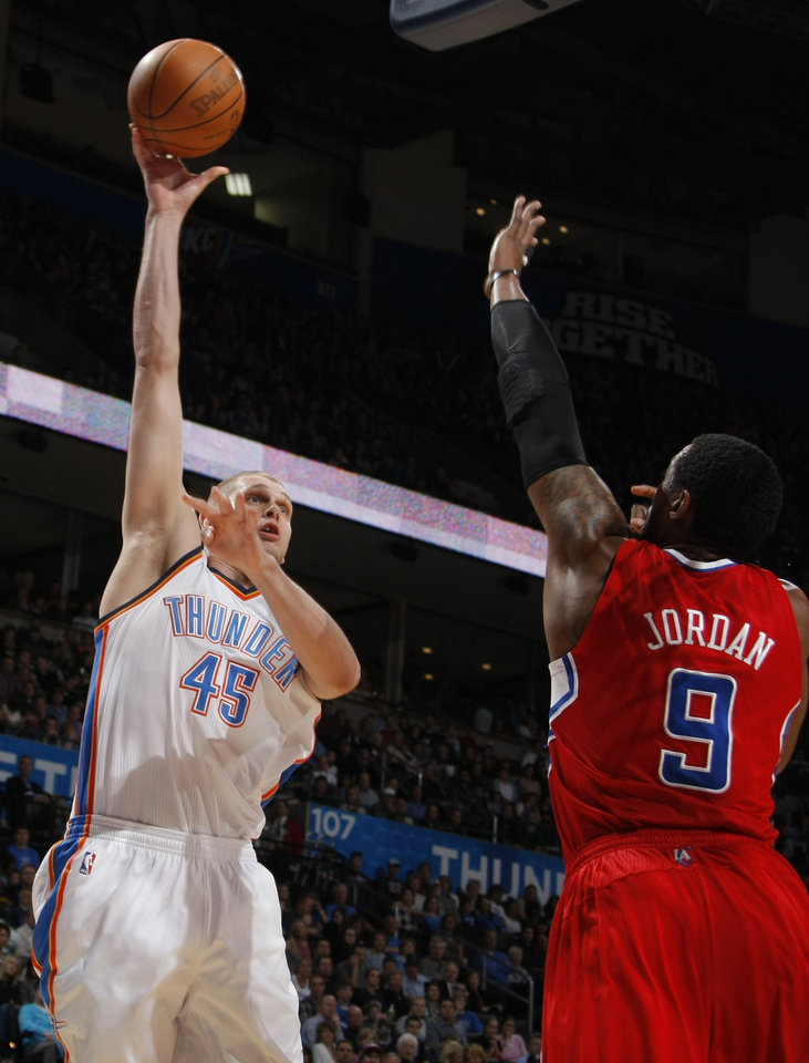 Photo - Oklahoma City's Cole Aldrich (45) shoots the ball over Los Angeles' DeAndre Jordan (9) during the NBA basketball game between the Oklahoma City Thunder and the Los Angeles Clippers at the Oklahoma CIty Arena, Tuesday, Feb. 22, 2011.  Photo by Bryan Terry, The Oklahoman