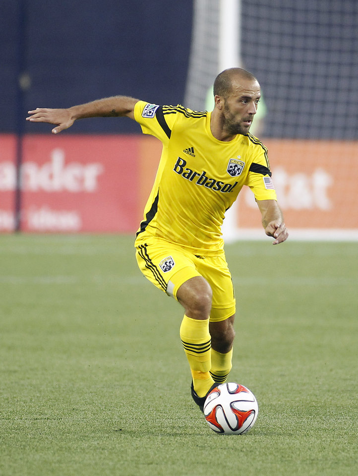 Photo - Columbus Crew's Federico Higuain dribbles the ball during the first half of an MLS soccer game against the New England Revolution, Saturday, July 26, 2014, in Foxborough, Mass. (AP Photo/Stew Milne)