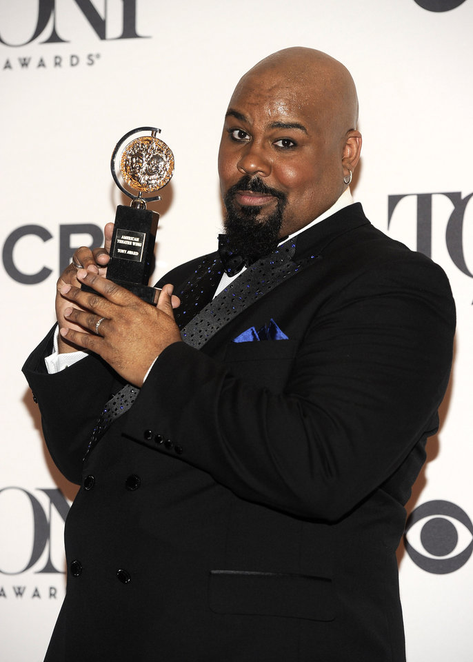 Photo - James Monroe Iglehart poses in the press room with his award for best performance by an actor in a featured role in a musical for