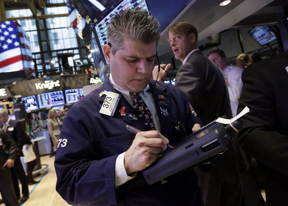 Photo - Trader John Panin, left, works on the floor of the New York Stock Exchange, Friday, Feb. 1, 2013. The Dow Jones industrial average briefly topped 14,000 on Friday morning, a milestone not seen since before the financial crisis rocked the markets and the world economy. Evidence that the U.S. economic recovery is firmly on track drove markets higher on Friday, adding to the cheer from good economic indicators out of Europe. (AP Photo/Richard Drew)