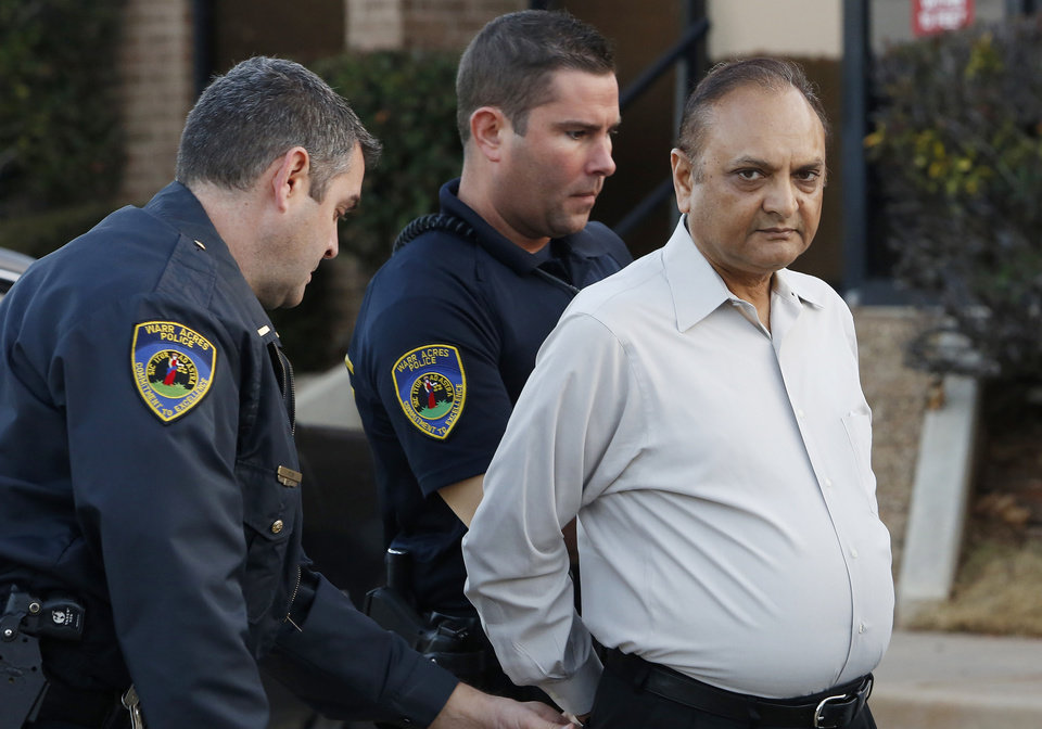 Photo -                    Warr Acres police officers adjust the handcuffs on abortion doctor Nareshkumar Patel, following his arrest Tuesday morning at his clinic, Outpatient Services for Women.                                                                             Photo by                                                          Paul B. Southerland, The Oklahoman