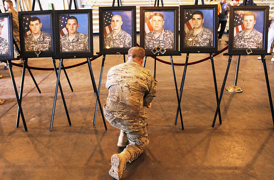 Spc. Brian Hall kneels in front of portraits of fallen soldiers Sunday during a welcome home ceremony for the National Guard 45th Infantry Brigade in Oklahoma City. Photos by Garett Fisbeck, For The Oklahoman