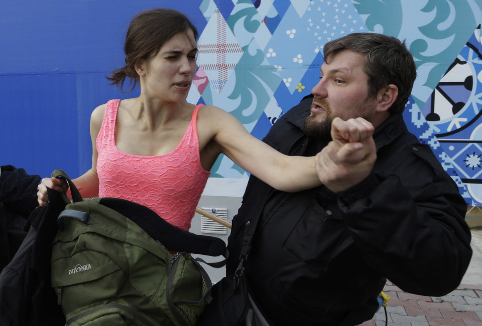 Photo - A russian security officer attacks Nadezhda Tolokonnikova and a photographer as she and fellow members of the punk group Pussy Riot, including Maria Alekhina, left, stage a protest performance in Sochi, Russia, on Wednesday, Feb. 19, 2014. The group had gathered in a downtown Sochi restaurant, about 30km (21miles) from where the Winter Olympics are being held. They ran out of the restaurant wearing brightly colored clothes and ski masks and were set upon by about a dozen Cossacks, who are used by police authorities in Russia to patrol the streets. (AP Photo/Morry Gash)