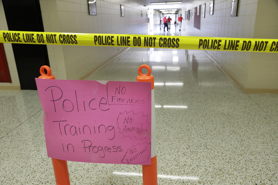 "In this photo taken July 11, 2013, a sign indicates ""police training in progress"" as police and weapons instructors walk in the hallways of Clarksville High School in Clarksville, Ark. Twenty Clarksville School District staff members are training to be armed security guards on campus. (AP Photo/Danny Johnston)"
