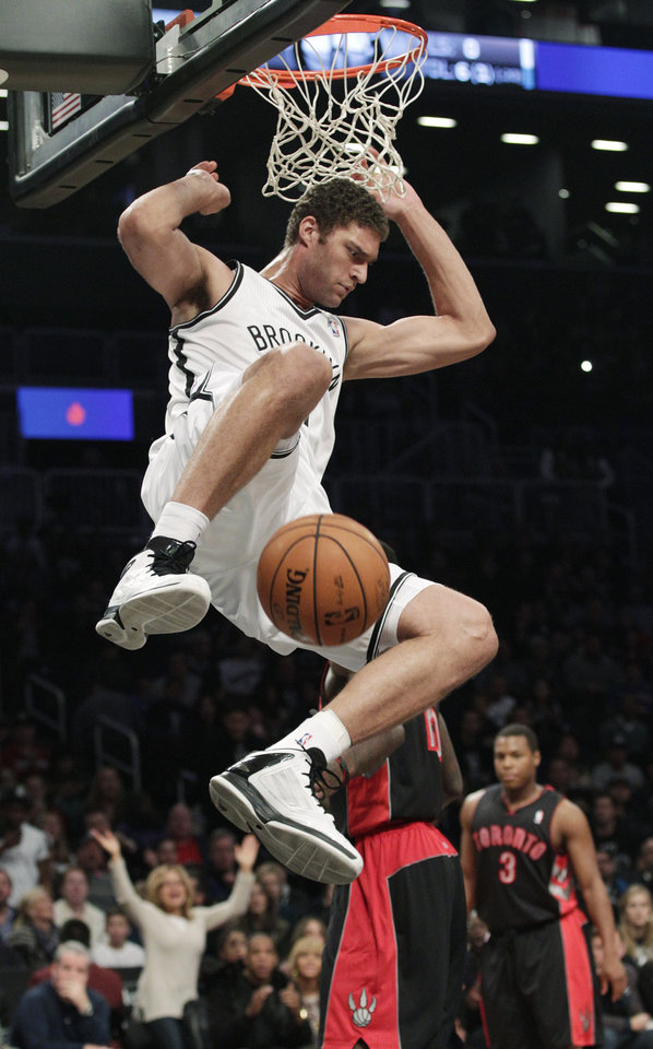 Brooklyn Nets\' Brook Lopez (11) dunks the ball as Toronto Raptors\' Kyle Lowry (3) looks on during the first half of an NBA basketball game, Saturday, Nov. 3, 2012, in New York. (AP Photo/Frank Franklin II)