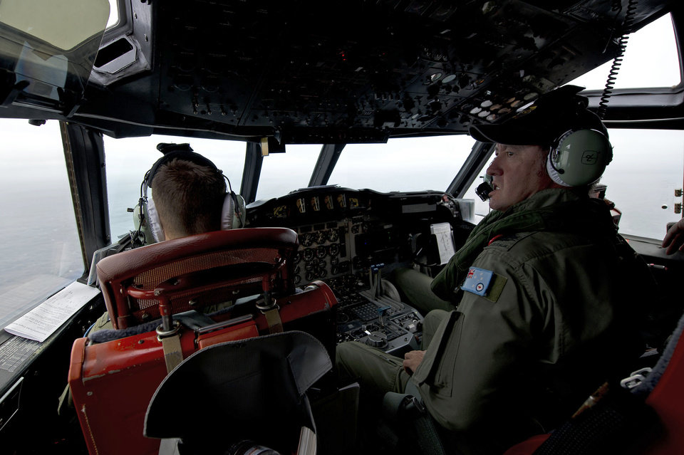 Photo - This Wednesday, March 19, 2014 photo released by the Australia Defence Department, shows Royal Australian Air Force Flight Engineer, Warrant Officer Ron Day from 10 Squadron, on board an AP-3C Orion over the Southern Indian Ocean off the Western Australian coast during a search operation for the missing Malaysian Airlines flight MH370. Australian Prime Minister Tony Abbott said Thursday that two objects possibly related to the missing flight have been spotted on satellite imagery in the Indian Ocean and an air force aircraft was diverted to the area to try to locate them. (AP Photo/Australia Defence Department, Hamish Paterson)