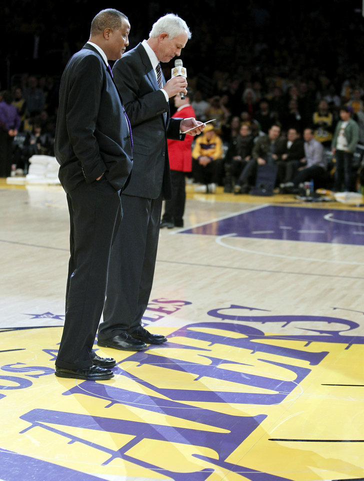 Los Angeles Lakers general manager Mitch Kupchak, right, speaks during a ceremony to retire the No. 52 jersey of former Laker Jamaal Wilkes at halftime of an NBA basketball game between the Lakers and the Portland Trail Blazers, Friday, Dec. 28, 2012, in Los Angeles. (AP Photo/Alex Gallardo)